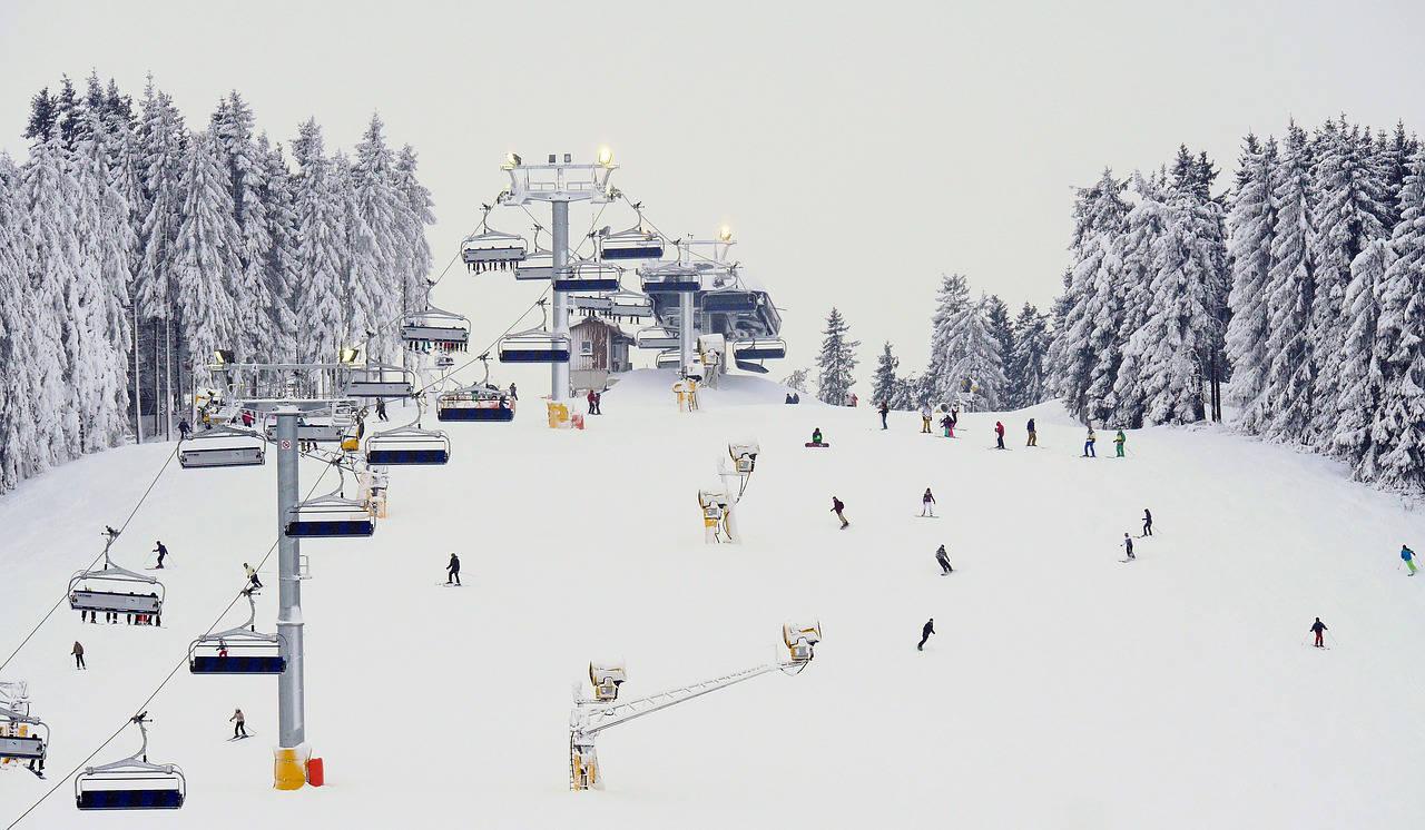 Pista da sci in inverno con sciatori e seggiovia